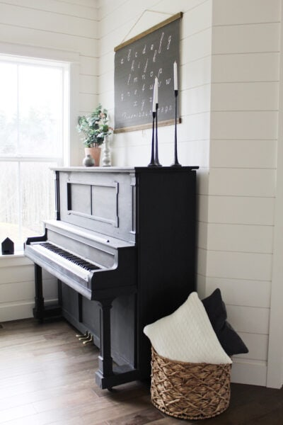 Every house needs a statement piece and this classic black piano would look great in any home! Loving this black painted piano against a shiplap wall, perfect farmhouse charm. #blackpiano #paintedblackpiano #blackpaintedpiano #farmhousepiano