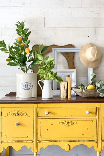 Welcome summer with these EASY entryway decor tips! #entryway #mantel #summerdecor #summertime #summerhomedecor #lemons #lemondecor #lemonhomedecor #yellowbuffet