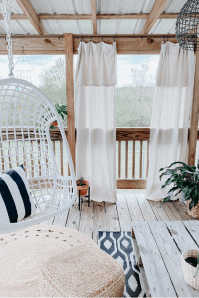 We can't decide what's the cutest part of this gorgeous boho farmhouse porch: the swing, the trendy jute circle rug or the cozy curtains. #bohofarmhouseporch #outdoorporchdecor #cozyporchideas #farmhouseporchdecor #bohostyleporch #juterugporch
