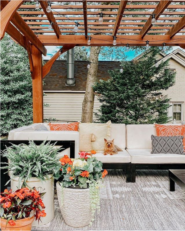 We love this gorgeous patio with its wood pergola, modern farmhouse patio furniture and colorful flower pots and topped it off with the cutest outdoor farmhouse style rug. #modernfarmhouserug #farmhouserug #outdoorrugideas #outdoorrugdecor