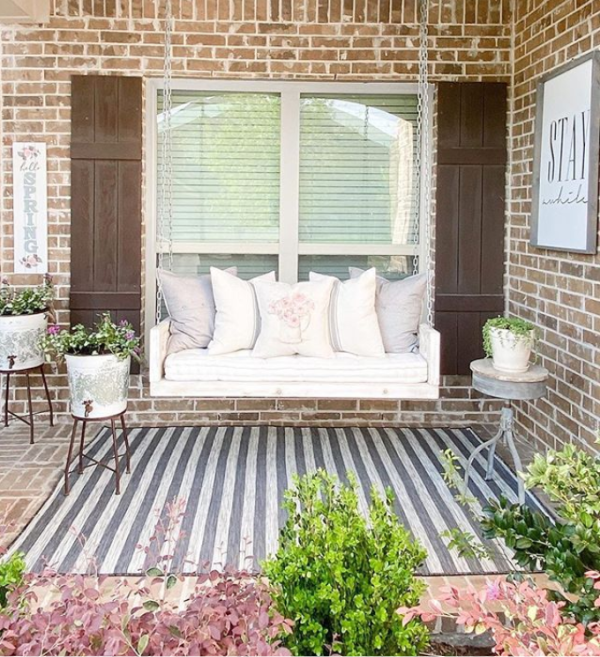 Such a pretty stripe outdoor rug for this cozy farmhouse porch. #stripeoutdoorrug #graywhitestripedrug #farmhouserug #outdoorrugideas #farmhouseporch #farmhouseporchswing