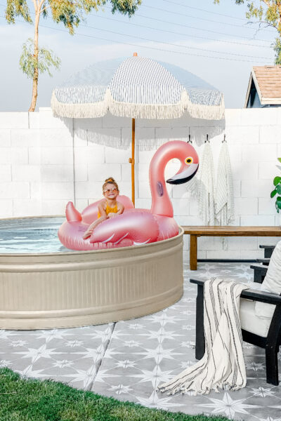 Paint a stock tank pool to match your style, such a fun spot to relax and cool off! #spraypaint #stencil #paintedfloors #diy #stocktankpool