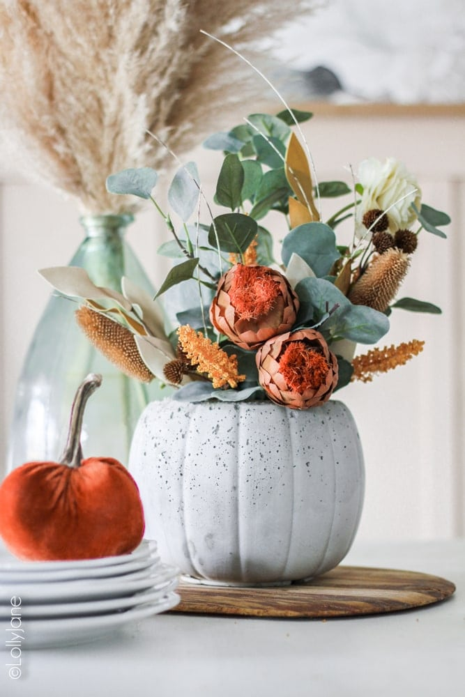 DIY Concrete Pumpkin Planter... perfect for fall and SURPRISE: the back has a jack-o-lantern face on it, perfect for Halloween! Made from a $1 treat bucket, this is a CHEAP yet CHIC project anyone can make! #diy #halloweendecor #falldecor #fallplanter #pumpkinplanter #diypumpkin #pumpkinfloralarrangement #fallfloralarrangement #fallflowers #pumpkinplanter