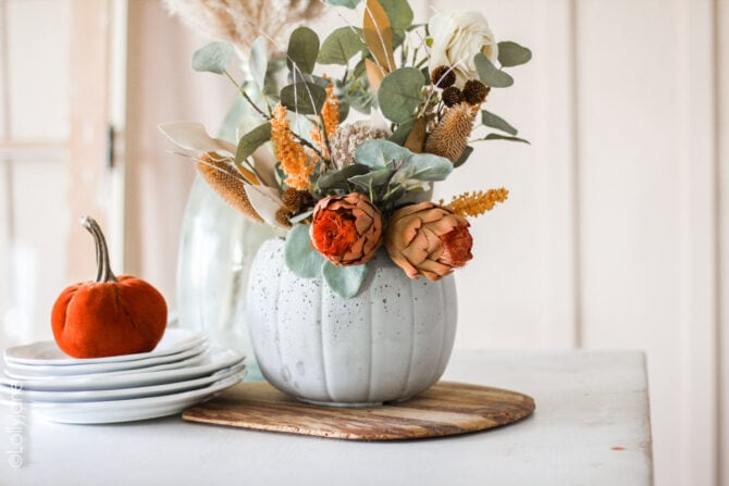 Made from a $1 treat bucket, this is a CHEAP yet CHIC project anyone can make! Darling concrete pumpkin planter. #halloweendecor #falldecor #fallplanter #pumpkinplanter #diypumpkin #pumpkinfloralarrangement #fallfloralarrangement #fallflowers #pumpkinplanter