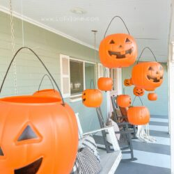 Level up dollar pumpkins for easy Halloween decoration. BONUS: They light up! #dollarpumpkindecor #plasticpumpkinshalloweendecor #hangingpumpkinsporchdecor #hangingpumpkinsoutdoordecor #halloweenoutdoordecor #halloweenporchdecor #halloweenporchpumpkindecor #howtohanghalloweendecor #diyhangingpumpkins