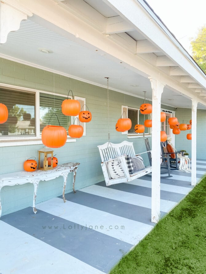 Check out this easy Halloween outdoor setup: use dollar store candy buckets as hanging pumpkins for cute Halloween porch decor! #hangingpumpkins #hangingpumpkinsporchdecor #floatingpumpkinsdecor #floatingpumpkinshalloweendecor #cheaphalloweendecor #halloweendiy #diyhalloweendecor