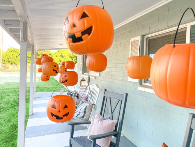 Have you seen those dollar pumpkins around? Turn those cheap plastic pumpkins into hanging porch decorations. Level up by adding remote control tea lights so they light up at night! #plasticpumpkincraft #dollarstorepumpkins #halloweendecor #halloweendecorations #candypumpkinbucketcrafts #pumpkinbucketdecor #halloweenporchdecor #plasticpumpkindecoratingideas #hangingpumpkinsonporch #hangingpumpkinbaskets
