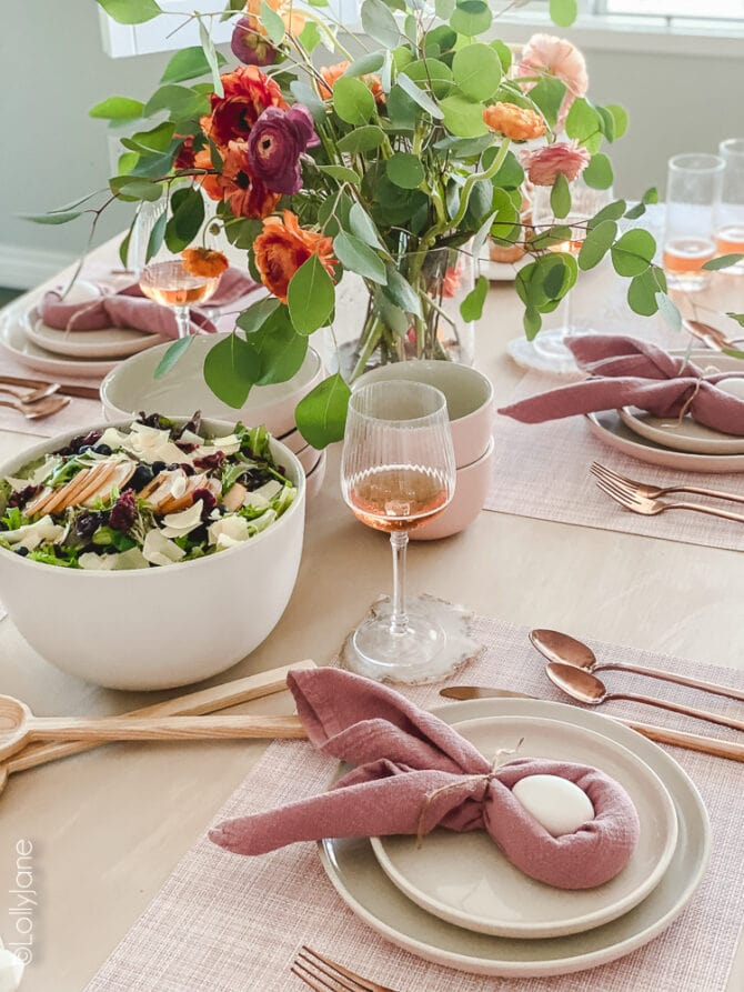 Pretty Easter decor that's perfect on your table top for brunch! Pink plates and rose gold flatware make this Easter table scape pop! #easter #easterdecor #easterdecorations #eastertablecape #springtablescape #tablescape #tabledecor #eastertabledecor