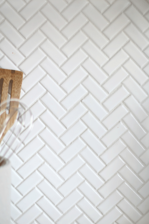 Enjoy a minimal look in the kitchen with white backsplash tiles. When installing a herringbone pattern, the overall look is simple and timeless. We love how our herringbone kitchen backsplash turned out.