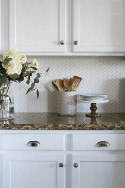 The herringbone tile pattern is a classic design that's always in style. Installing this herringbone kitchen backsplash was an affordable way to update our tract home kitchen.